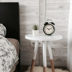 Black Alarm Clock At 1010 On White Wooden Table Near Table