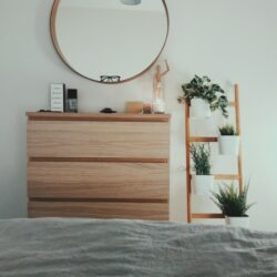 Brown Wooden 3 Drawer Chest With Round Brown Wooden Framed Mirror In Front Of Bed Inside Room