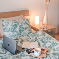 Silver Macbook On Top Of White And Blue Bedding Set